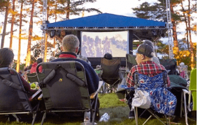 people in camp chairs watching a movie outside