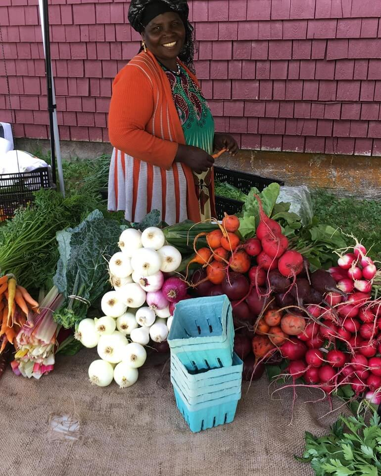 a woman tending her vegetables at a farmer's market